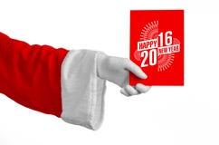 Tema 2016 för jul och för nytt år: Santa Claus hand som rymmer ett rött gåvakort på en vit bakgrund i studio isolerat Arkivbild