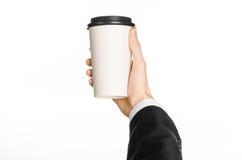 Tema för kaffe för affärsluncher: affärsman i en svart dräkt som rymmer en vit kopp kaffe för tomt papper med en brun plast- lock Royaltyfria Foton
