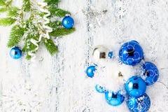 Tema för nytt år: Julgran-, blått- och silverbollar, snö, snöflingor som är slingrande Royaltyfri Foto