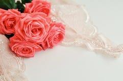 Tema femenino delicado Las rosas coralinas rosadas tienden color en un pálido - collar rosado del sujetador y de la perla en un f imagen de archivo