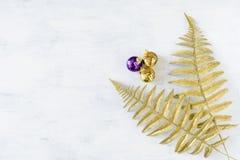 Tema festivo do feriado do Natal com o ornamento violeta dourado do Natal e as folhas decorativas da samambaia do ouro fotos de stock royalty free