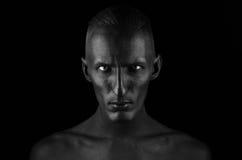 Tema gótico e de Dia das Bruxas: um homem com pele preta é isolado em um fundo preto no estúdio, a arte corporal da morte preta Imagem de Stock