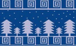 Tema hecho punto del invierno con los abetos y la nieve en azul Foto de archivo