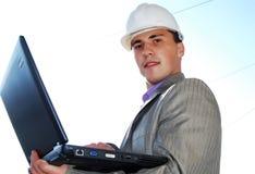 Tema industriale: costruttore e computer portatile. Immagini Stock Libere da Diritti