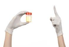Tema médico: la mano del doctor en los guantes blancos que sostienen un envase transparente con el análisis de la orina en un fon Imagenes de archivo