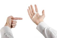 Tema médico: la mano del doctor que sostiene un termómetro para medir la temperatura del paciente en un fondo blanco Foto de archivo libre de regalías