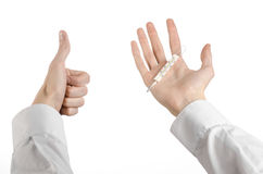 Tema médico: la mano del doctor que sostiene un termómetro para medir la temperatura del paciente en un fondo blanco Imagen de archivo libre de regalías