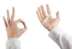 Tema médico: la mano del doctor que sostiene un termómetro para medir la temperatura del paciente en un fondo blanco Fotos de archivo libres de regalías