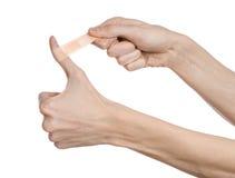 Tema medico: per la mano di un uomo il pronto soccorso incollato del gesso medico intonaca la pubblicità su un fondo bianco Immagine Stock
