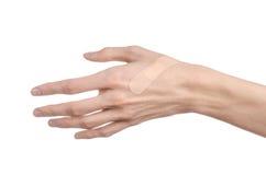 Tema medico: per la mano di un uomo il pronto soccorso incollato del gesso medico intonaca la pubblicità su un fondo bianco Immagine Stock Libera da Diritti