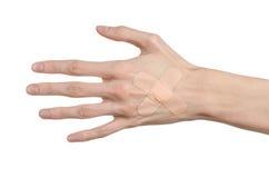 Tema medico: per la mano di un uomo il pronto soccorso incollato del gesso medico intonaca la pubblicità su un fondo bianco Fotografia Stock