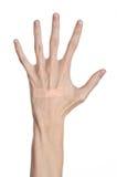 Tema medico: per la mano di un uomo il pronto soccorso incollato del gesso medico intonaca la pubblicità su un fondo bianco Fotografia Stock Libera da Diritti