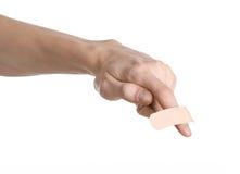 Tema medico: per la mano di un uomo il pronto soccorso incollato del gesso medico intonaca la pubblicità su un fondo bianco fotografie stock