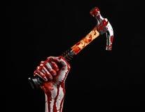 Tema sangriento de Halloween: mano sangrienta que sostiene un martillo sangriento aislado en un fondo negro Imagen de archivo libre de regalías