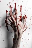 Tema sanguinoso di Halloween: la stampa sanguinosa della mano su un bianco lascia la parete sanguinosa Fotografia Stock