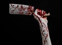 Tema sanguinoso di Halloween: mano sanguinosa che giudica un grande coltello da cucina sanguinoso su un fondo nero isolato Fotografia Stock