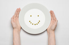 Tema sano de la comida: manos que sostienen una placa de guisantes verdes en una opinión de sobremesa blanca Foto de archivo