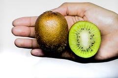 Tema sano de la consumición y de la dieta: Mano humana que sostiene un medio kiwi aislado en un fondo blanco en el estudio fotografía de archivo