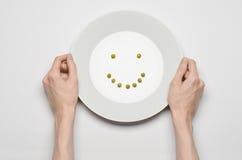 Tema saudável do alimento: mãos que guardam uma placa de ervilhas verdes em uma opinião de tampo da mesa branca Imagem de Stock Royalty Free