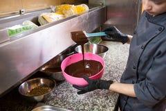 Tema som lagar mat choklad N?rbild av en hand Den unga Caucasian kvinnakocken med tatueringen och i likformig f?rbereder sig att  fotografering för bildbyråer