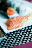 Temaki sushi, sushi, lax och wasabi på en platta Arkivfoto