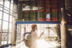Temalopp och tranosport Härlig ung caucasian kvinna i station för drev för klänning- och ryggsäckanseende inre eller terminallook arkivbilder
