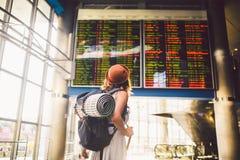 Temaloppkollektivtrafik anseende för ung kvinna med baksida i klänning och hatt bak ryggsäcken och campa utrustning för att sova, arkivbild