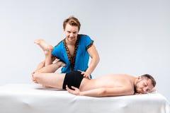 Temamassage och kroppomsorg En stilig Caucasian man i blått likformig och skägg gör sträckning, läker, diagnosen av muskelnollan royaltyfria bilder
