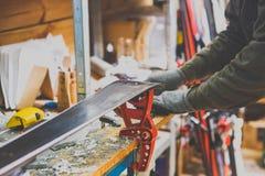 Temareparationer och underhåll av skidar Den manliga arbetaren reparerar arbetskläder som applicerar vaxet på glidningsyttersidan arkivfoto