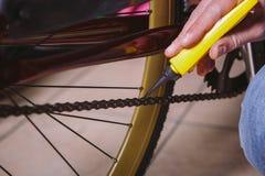 Temareparationscyklar Närbild av ett Caucasian bruk för hand för man` s ett Chain smörjmedel i en gul smörjapparat för llubricato Royaltyfri Foto