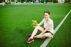 Temasport och hälsa Härligt ung flickasammanträde som vilar på grönt gräs, konstgjord torvastadion som vilar den törstiga drinkfl royaltyfri bild