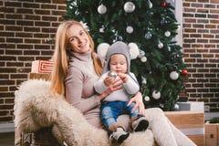 Tematów wakacji zimy Bożenarodzeniowy nowy rok Młoda elegancka Kaukaska matka trzyma jej syna w jej rękach dla 1 roku w śmiesznej obrazy royalty free