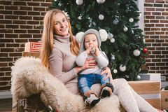 Tematów wakacji zimy Bożenarodzeniowy nowy rok Młoda elegancka Kaukaska matka trzyma jej syna w jej rękach dla 1 roku w śmiesznej zdjęcie royalty free