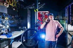 Temat är små och medelstora företag Stående av en ung man ägaren av ett cykelseminarium för reparation och underhåll av cyklar Gr royaltyfria bilder