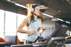 Temat är sporten och musik En härlig uppblåst kvinna kör i idrottshallen på en trampkvarn På hennes huvud är den stora vita hörlu royaltyfri foto