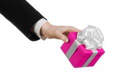 Temat av berömmar och gåvor: handen som rymmer en gåva slågen in i rosa färger, boxas med det vita bandet, och pilbågen, den mest Arkivfoto