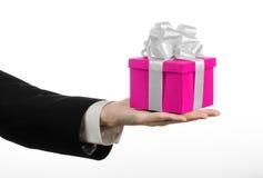 Temat av berömmar och gåvor: handen som rymmer en gåva slågen in i rosa färger, boxas med det vita bandet, och pilbågen, den mest fotografering för bildbyråer