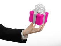Temat av berömmar och gåvor: handen som rymmer en gåva slågen in i rosa färger, boxas med det vita bandet, och pilbågen, den mest Royaltyfri Bild