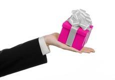 Temat av berömmar och gåvor: handen som rymmer en gåva slågen in i rosa färger, boxas med det vita bandet, och pilbågen, den mest Royaltyfria Bilder