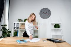 Temat biznesowa kobieta przy pracą Piękna młoda caucasian kobieta biznesowego mężczyzny pracująca pozycja w biurze blisko stołu,  zdjęcie royalty free