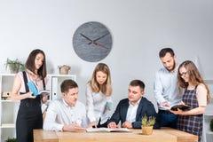 Temat jest biznesowy i praca zespołowa Grupa młodzi Kaukascy ludzie urzędników trzyma spotkania, odprawa, pracuje z papierami zdjęcie stock