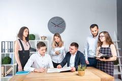Temat jest biznesowy i praca zespołowa Grupa młodzi Kaukascy ludzie urzędników trzyma spotkania, odprawa, pracuje z papierami zdjęcie royalty free