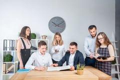 Temat jest biznesowy i praca zespołowa Grupa młodzi Kaukascy ludzie urzędników trzyma spotkania, odprawa, pracuje z papierami fotografia stock