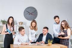 Temat jest biznesowy i praca zespołowa Grupa młodzi Kaukascy ludzie urzędników trzyma spotkania, odprawa, pracuje z papierami fotografia royalty free