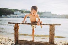 Temat jest dziecka i lato plaży wakacje Mała Kaukaska chłopiec wspina się up na drewnianej ławce na brzeg rzeki w pogodnej sumie Obraz Stock