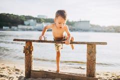 Temat jest dziecka i lato plaży wakacje Mała Kaukaska chłopiec wspina się up na drewnianej ławce na brzeg rzeki w pogodnej sumie Obrazy Stock