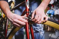 Temat naprawy rowery Zakończenie Kaukaski mężczyzna ` s ręki use handtool sześciokąt ustawiający przystosowywać obręczy hamulce n fotografia stock