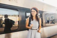 Temat podróż i kolej Portret młoda caucasian kobieta z toothy uśmiech pozycją przy dworca pociągu tłem z backpac obraz royalty free