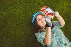 Temat technologia i sport Piękny caucasian kobieta uczeń z toothy uśmiechów kłamstw z powrotem odpoczynku zieloną trawą w rowerow obrazy royalty free