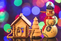 tematu nowy rok 2017 rok postacie z dekoracyjnym domem, jedlinowym drzewem i bałwanem na światła tle, Zdjęcie Stock